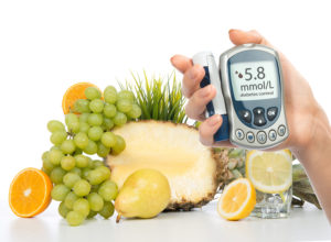 Diabetes concept glucose meter in hand and healthy organic food lemon water pear grapes fresh orange isolated on a white background