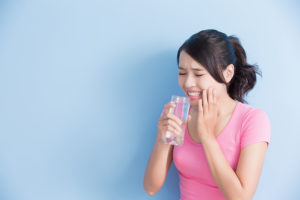 woman drink water with sensitive teeth isolated on blue background